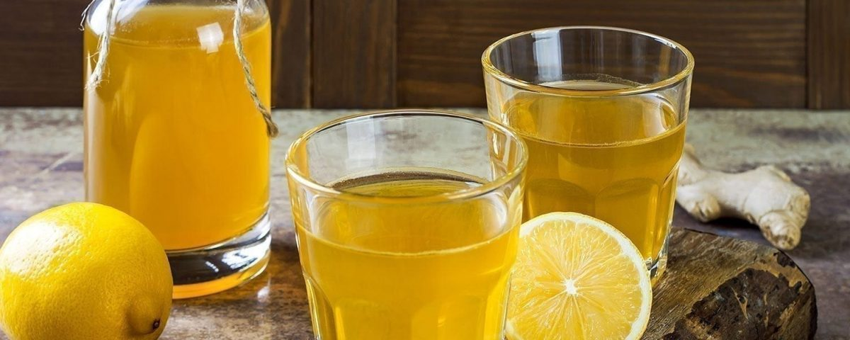 A glass of orange juice next to a cup of beer on a table